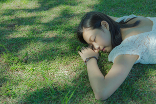 芝生に寝転ぶ女性の写真素材 [FYI02597531]