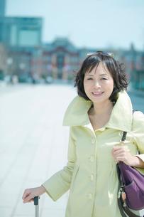 キャリーバッグを持つシニア女性の写真素材 [FYI02597538]