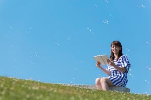 ベンチに座って本を読む笑顔の女性の写真素材 [FYI02597593]
