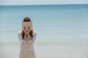 本で顔を隠す女性の写真素材 [FYI02597626]