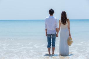 波打ち際で手をつなぐカップルの後姿の写真素材 [FYI02597629]