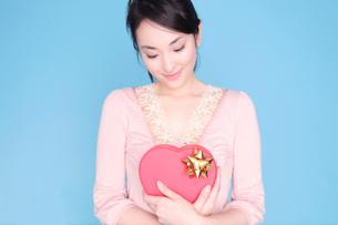 ハート形のプレゼントを持った女性の写真素材 [FYI02599114]