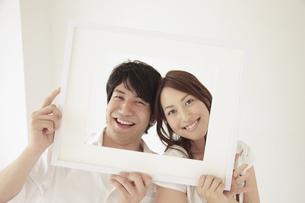一つの額縁から顔を覗かせるカップルの写真素材 [FYI02600506]