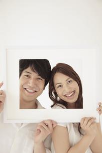 一つの額縁から顔を覗かせるカップルの写真素材 [FYI02600741]