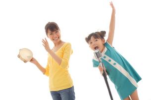 歌う女の子とタンバリンをたたくお母さんの写真素材 [FYI02604015]