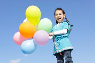 青空の下カラフルな風船を持つ女の子の写真素材 [FYI02604503]