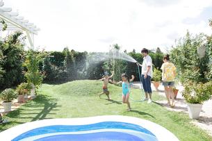 庭でシャワーの水遊びをする親子の写真素材 [FYI02604575]
