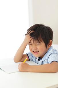 勉強中に頭を抱える男の子の写真素材 [FYI02604613]
