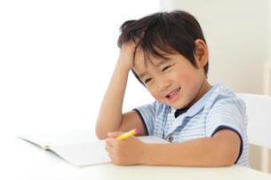 勉強中に頭を抱える男の子の写真素材 [FYI02604721]