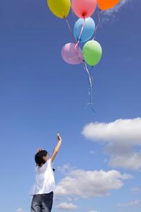 青空の下カラフルな風船を飛ばす女の子の写真素材 [FYI02604728]