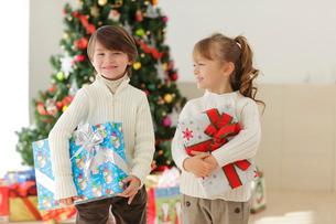 クリスマスツリーの前でプレゼントを抱える男の子と女の子の写真素材 [FYI02604743]