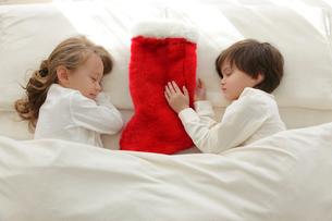赤い靴下とベッドで眠る幼い兄妹の写真素材 [FYI02605029]