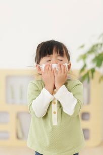 マスクをしてくしゃみをする女の子の写真素材 [FYI02606793]