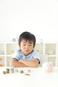 貯金箱の前で悩む男の子の写真素材 [FYI02607471]