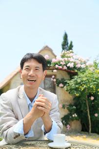 バラの庭でコーヒーを飲む中年男性の写真素材 [FYI02607605]