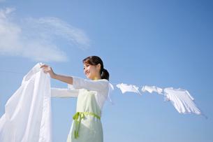 青空の下で家族の洗濯物を干す女性の写真素材 [FYI02607696]