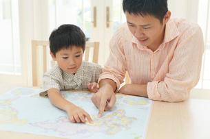 テーブルで地図を広げるお父さんと子どもの写真素材 [FYI02607706]