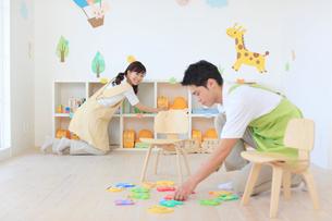 教室の片づけをする男女の幼稚園の先生の写真素材 [FYI02607736]