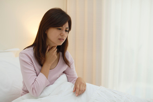 体調不良で喉を押さえる女性の写真素材 [FYI02607768]
