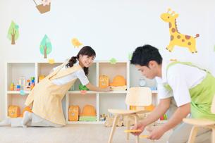 教室の片づけをする男女の幼稚園の先生の写真素材 [FYI02607817]