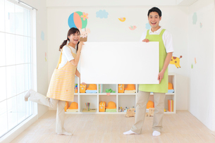ホワイトボードを持つ男女の幼稚園の先生の写真素材 [FYI02607851]