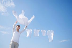 青空の下で家族の洗濯物を干す女性の写真素材 [FYI02607902]