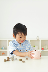 貯金箱の中身を確認する男の子の写真素材 [FYI02608006]