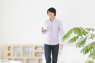 ホームオフィスで仕事中に休憩をする男性の写真素材 [FYI02608066]