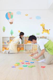 教室の片づけをする男女の幼稚園の先生の写真素材 [FYI02608196]