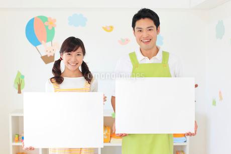 ホワイトボードを持つ男女の幼稚園の先生の写真素材 [FYI02608217]