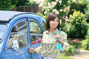 水色の可愛い車から降りる若い女性の写真素材 [FYI02608398]