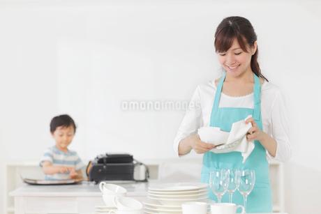食器を片づけるお母さんと勉強をする男の子の写真素材 [FYI02608400]