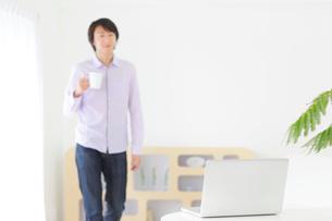ホームオフィスで仕事中に休憩をする男性の写真素材 [FYI02608423]