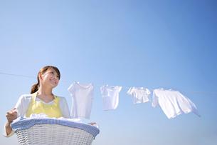 青空の下で家族の洗濯物を干す女性の写真素材 [FYI02608587]