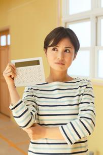 計算機を手に建築費用に悩む女性の写真素材 [FYI02608608]