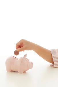 貯金箱にお金を入れる子どもの手の写真素材 [FYI02608692]