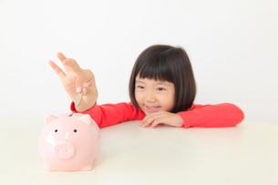 貯金箱にお金を入れるおかっぱの女の子の写真素材 [FYI02609000]