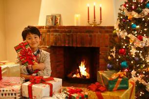 クリスマスツリーとプレゼントに囲まれたと男の子の写真素材 [FYI02609162]