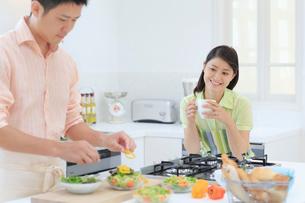 料理をする夫と見守る妻の写真素材 [FYI02609170]
