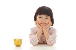 貯金箱と頬杖をついて考える女の子の写真素材 [FYI02609286]