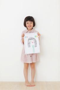 お母さんの絵を持つおかっぱの女の子の写真素材 [FYI02609297]
