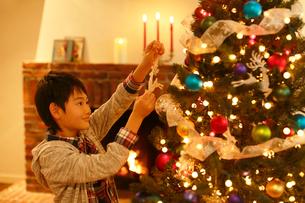 クリスマスツリーに飾り付けをする男の子の写真素材 [FYI02609362]