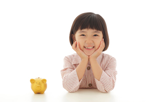 貯金箱と頬杖をついて考える女の子の写真素材 [FYI02609369]