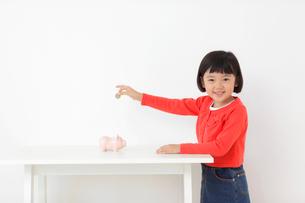 貯金箱にお金を入れるおかっぱの女の子の写真素材 [FYI02609403]