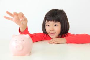 貯金箱にお金を入れるおかっぱの女の子の写真素材 [FYI02609675]