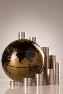 高く積まれた硬貨と地球儀の写真素材 [FYI02611578]