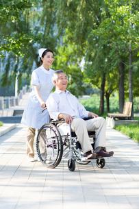 車椅子に乗った男性と看護婦の写真素材 [FYI02612083]