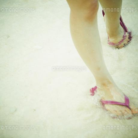 波打ち際を歩く女性の足元の写真素材 [FYI02614241]