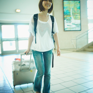 スーツケースを持って歩く女性の写真素材 [FYI02614282]