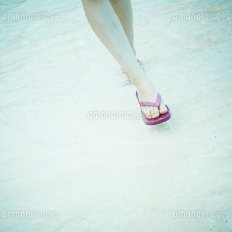 波打ち際を歩く女性の足元の写真素材 [FYI02614391]